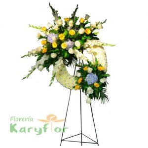 Corona especial de condolencias elaborado en tripode con finas rosas, lilium, gladiolos, gerberas y follaje. Se puede elaborar en distintos colores de rosa previa coordinación.