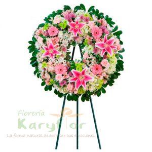 Corona de condolencias elaborado en tripode con finas rosas, lilium, gerberas, variedad de flores y follaje. Se puede elaborar en distintos colores de rosa previa coordinacion.