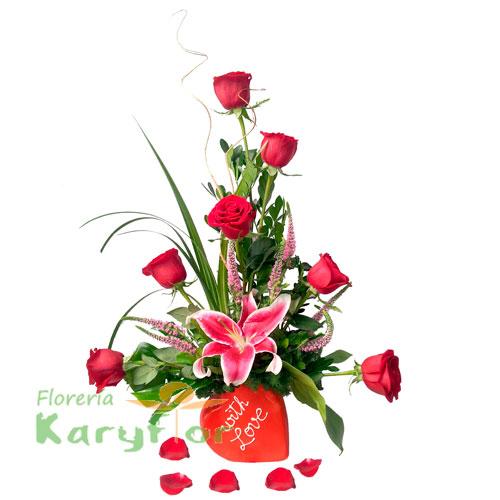 """Arreglo floral elaborado en base de corazón con la frase """"With Love"""", contiene 7 rosas, lilum , flores y fino follaje. Pueden agregar adicionales, chocolates, globos y peluches ingresando a la opción de regalos."""