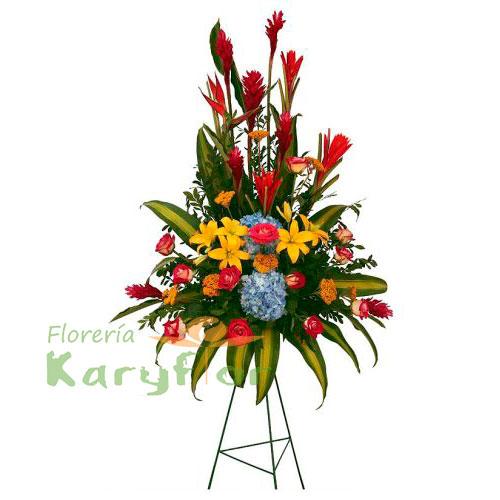 Arreglo floral compuesto por finas rosas, hortencias, lilium, gerberas, ginger, variedad de flores, palmeras y fino follaje elaborado en tripode. Incluye tarjeta de dedicatoria.