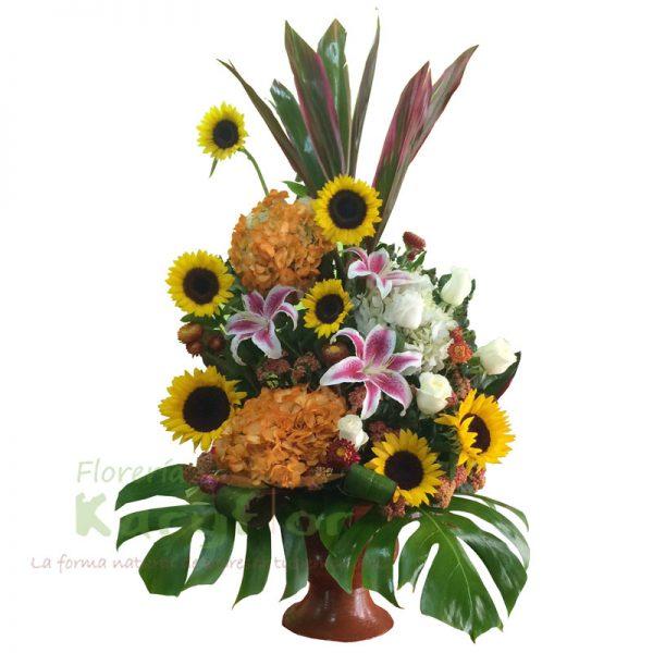 Arreglo floral compuesto por rosas importadas, calas amarillas, claveles, fino follaje en florero de cerámica. Incluye tarjeta de dedicatoria.