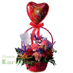 Arreglo floral en canasta decorada, elaborado con flores primaverales y fino follaje. Incluye globo de amor Nº 9 y tarjeta dedicatoria.