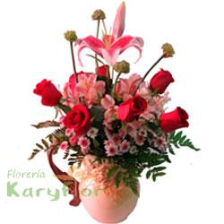 Arreglo floral elaborado con 7 rosas, astromelia, lilium, flores variedas y fino follaje, en jarrón de cerámica decorada. Incluye tarjeta de dedicatoria.