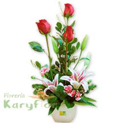 Lindo arreglo floral elaborado en base de cerámica blanca, contiene 3 rosas importadas, lilium perfumado, claveles, fino follaje. Incluye tarjeta de dedicatoria.