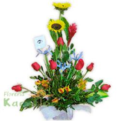 Arreglo floral elaborado en base de cerámica con papel importado, contiene 7 rosas importadas, ginger, girasoles, 3 iris, astromelias, fino follaje. Incluye tarjeta de dedicatoria.